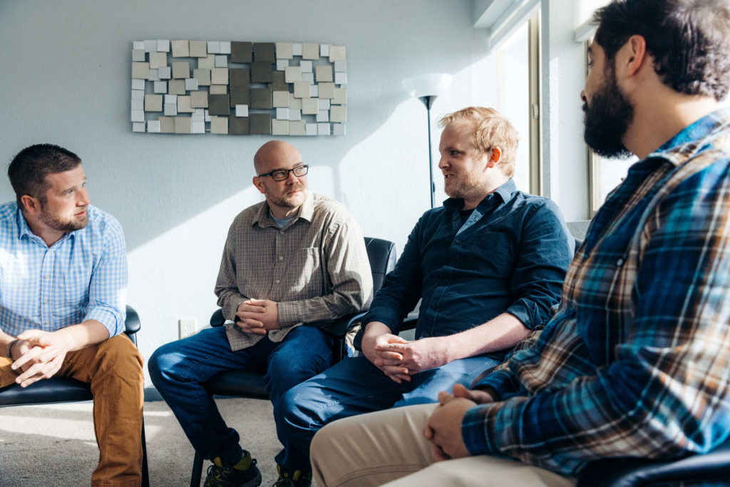 A group of men sit and talk