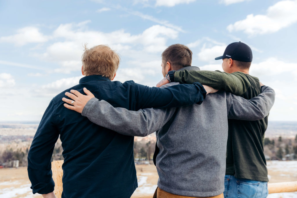 Three white men stand arms over each other's shoulders staring at the blue sky