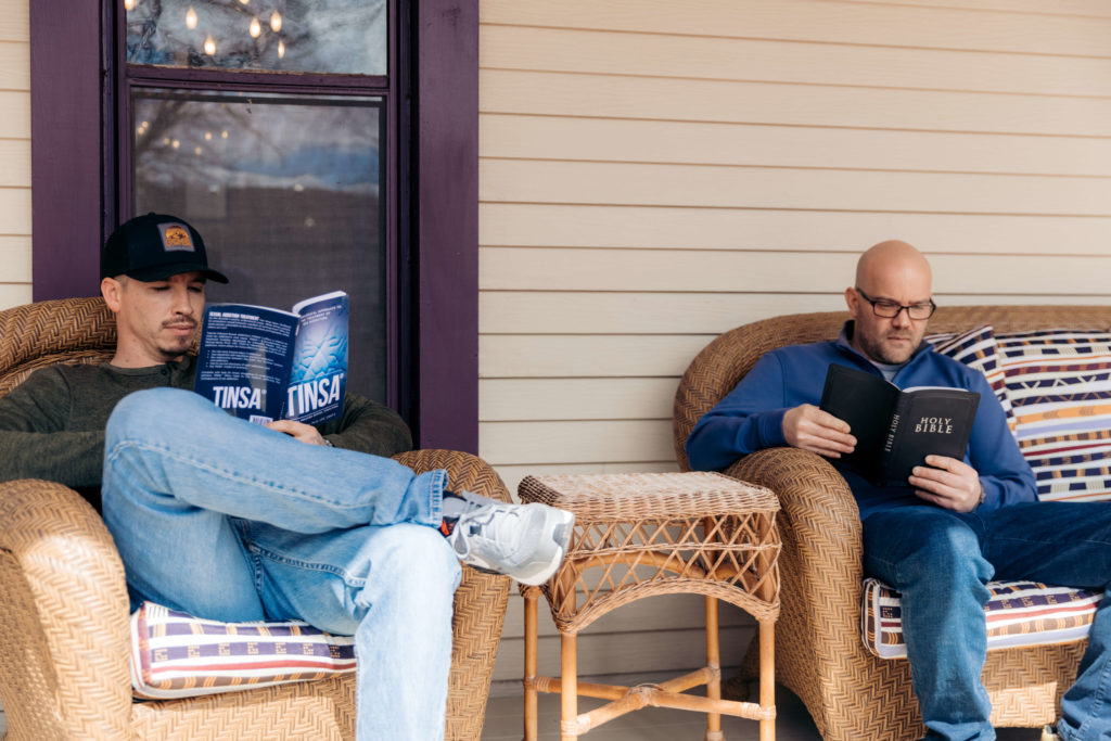 """Two men sit on a porch reading. One has a book cover showing """"TINSA"""""""